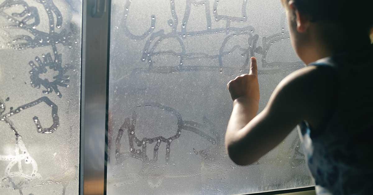 Gutt som tegner på kondens på vindu.