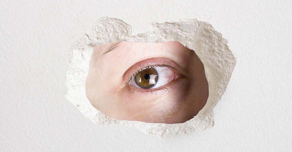 Ett øye ser gjennom hull i veggen